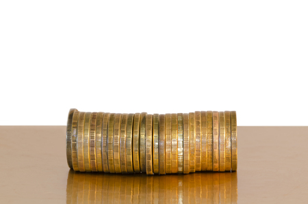 A stack of coins, placed horizontally on a Golden surface, isolated on white background