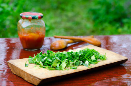 Still life of chopped green onions on a cutting Board on the wet surface of the table, banks with peppers in tomato sauce and wooden spoons in nature photo