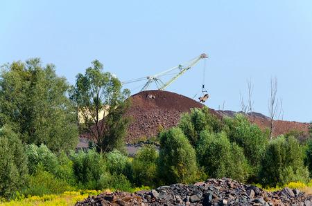 quartzite: The excavator on formation of quartzite dump violates the natural landscape
