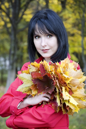 pensiveness: Girl with a bouquet of yellow leaves Stock Photo