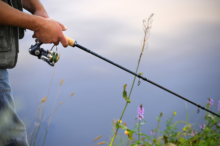 pescador: La pesca en el río. Un pescador con una caña de pescar en la orilla del río. Hombre Pescador atrapa un pez. El concepto de una escapada rural. Artículo sobre la pesca.