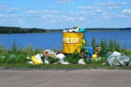 household waste: Overflowing barrel with household waste and waste disposal on the waterfront