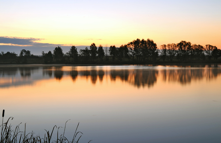 Sunrise landscape with a lake and the mist over the water Archivio Fotografico