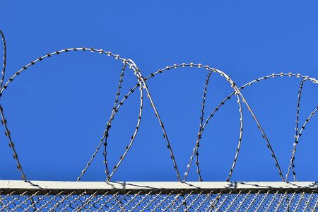 Fence with a barbed wire against the blue sky. Illustration of the concept of freedom or liberty.
