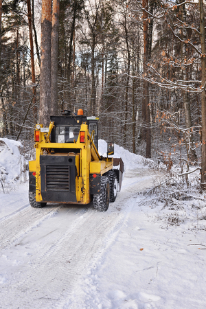 tree removal service: The tractor clears snow from the road in the woods Stock Photo