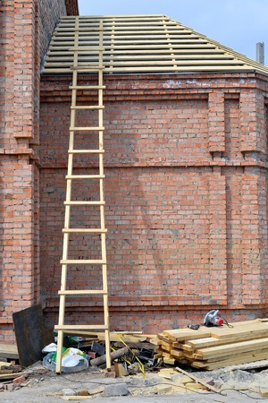 rungs: Wooden stairs on a brick wall.