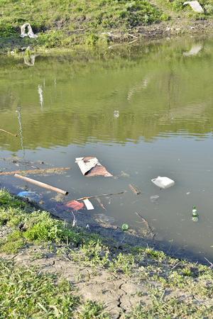 mundo contaminado: La basura, los residuos flotantes en el estanque contaminado. Foto de archivo