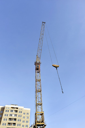 reinforcement: Crane and building construction site against blue sky