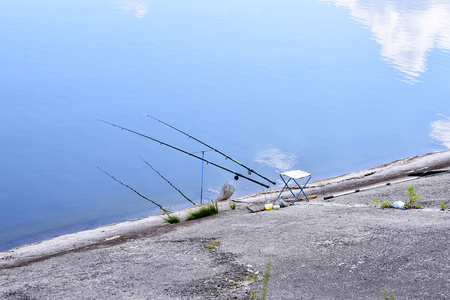 fishing equipment: Chair with fishing poles and fishing equipment at the lake
