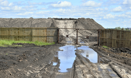 fertile land: Dirt road, a pool and a lot of stored in the open air ground for a closed fence
