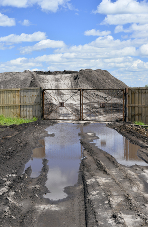 Dirt road, a pool and a lot of stored in the open air ground for a closed fence