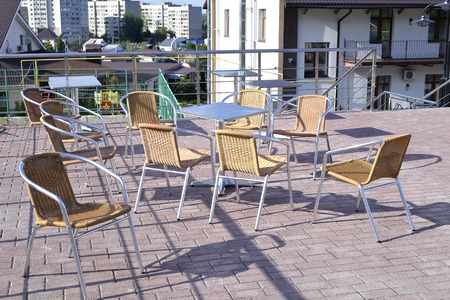 legs open: Wicker chairs with metal legs and racks are in an open cafe area