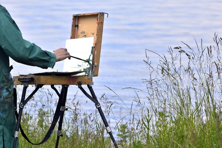Hands of the artist with a brush, paint a picture on an easel in the open air