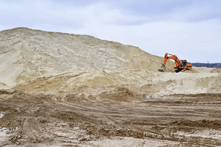 gravel pit: Working digger in a quarry produces sand