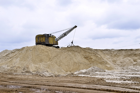 sand quarry: Working digger in a quarry produces sand. Working digger in a quarry produces sand Stock Photo