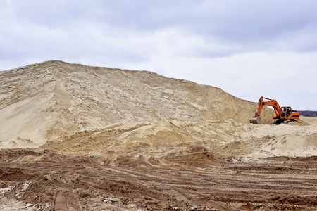 gravel pit: Working digger in a quarry produces sand.