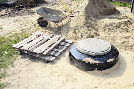 Construction site with new armed manholes, cart, sand and equipment.