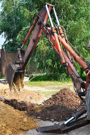 Excavator bucket digging a trench in the dirt ground.