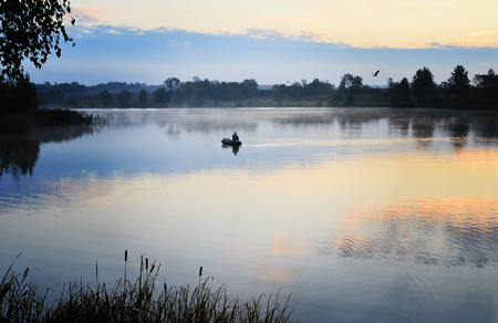 A fisherman in a boat floating on the water in the dawn sun in the fog Stock Photo