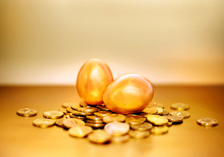 Gold coins and golden eggs, the concept of financial growth. Stock Photo