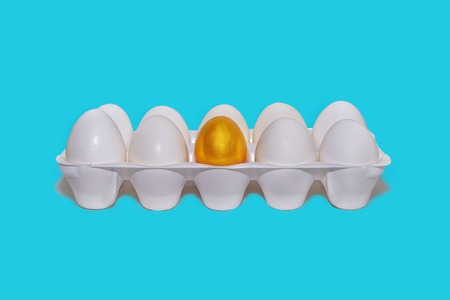 Tray with white eggs, one gold, the concept of the beginning of financial success Stock Photo
