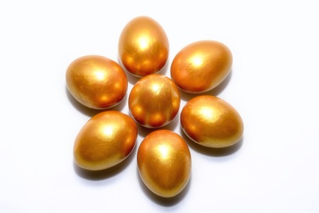 Golden eggs lie in the form of a flower on a white background, the concept of financial success. Stock Photo