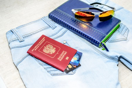 Red russian Passport with bank cards, glasses and notepad lie on jeans. The concept of travel