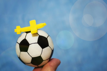 Yellow toy airplane on a soccer ball. The concept of flying to the football championship.