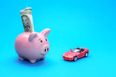 Pink piggy bank with a car on the table. Tinted. Concept of saving finances and contributions to property
