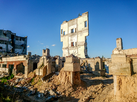 The ruins of a large destroyed building, pieces of stone, concrete, clay and metal against the blue clear sky