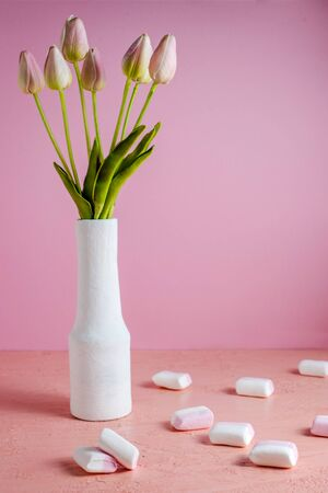 Copyspace with colorful mini marshmallows on a table next to pink tulips in a white vase on a pink background