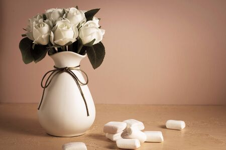 Copyspace with colorful mini marshmallows on a table next to white roses on a pink background