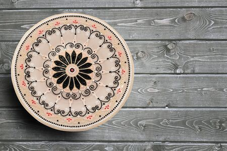 Decorative ceramic plate, hand painted dot pattern with acrylic paints on a gray wooden background. Copy space