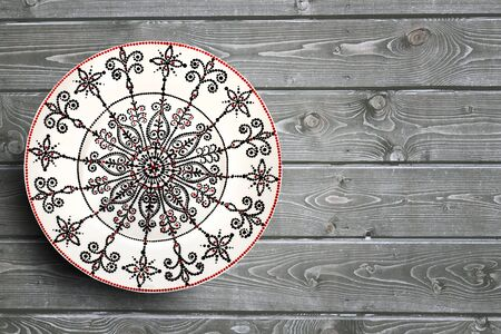 Set of decorative ceramic plates hand painted dot pattern with acrylic paints on a gray wooden background. Copy space