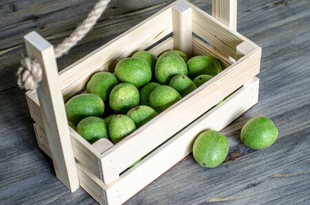 Young fruits of walnuts in a green shell in a wooden box