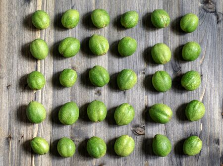 Young green fruits of walnuts lie in rows on a gray wooden background Reklamní fotografie