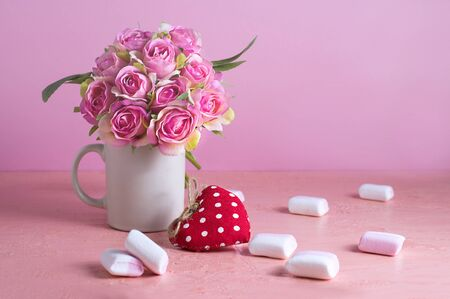 Small white and pink marshmallows are scattered on a pale pink background next to a vase of roses. Place for text. Banco de Imagens