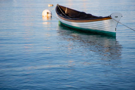 green boat: Vintage wooden white, orange and green boat and buoy moored on calm blue waters on Martha s Vineyard