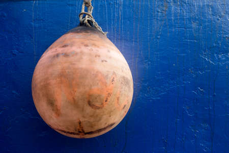Rust coloured weathered buoy against a vivid blue boat hull