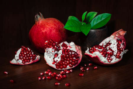 segments: Pomegranate with broken segments, still life on dark background