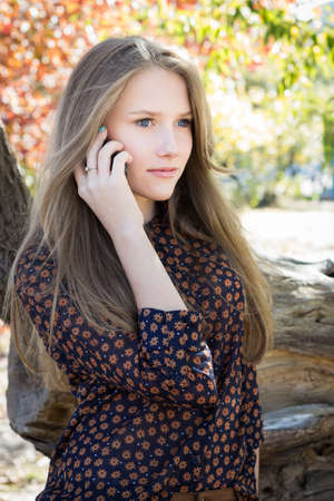 Young beautiful girl calling by mobile phone in park photo