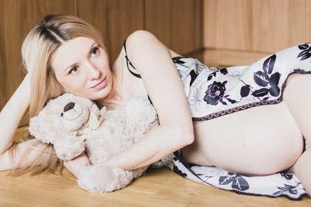 Beautiful pregnant woman in sexy nightwear lying on floor  with teddy bear