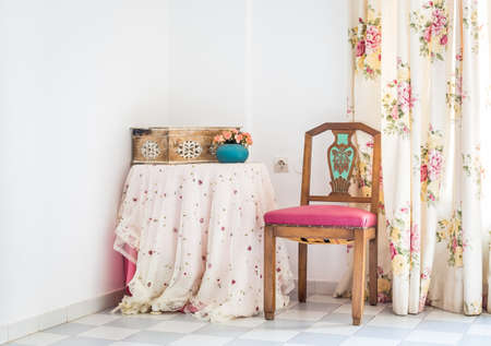 cortinas: Interior de estilo vintage con mesa, silla tallada y cortina floral Foto de archivo