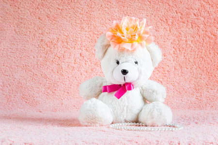barrette: White teddy bear toy with orange flower barrette on head