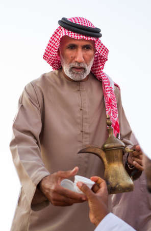 Bedouin man offers arabic coffee in Al wathba festival in September 12, 2014 Abu Dhabi UAE