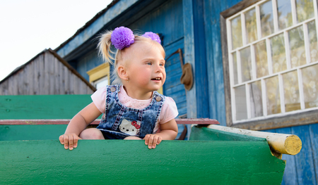 A little girl with bows looking surprisingly sitting on a cart on the background of a village house