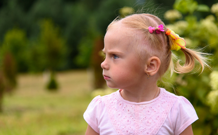 A little discontented indignant girl in nature