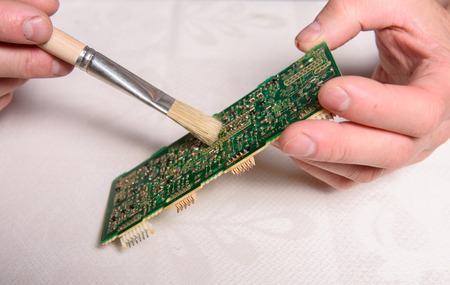 Circuit board with hand holding brush, cleaning board.