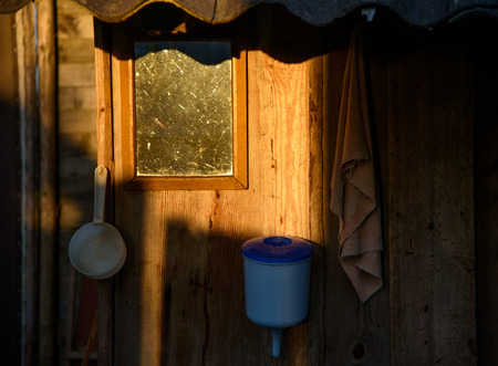 Village place for washing. A wooden wall of the shed. Hygiene in the early morning.