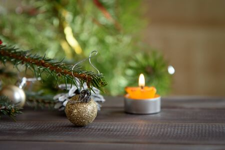 Christmas, decoration on a wooden table. Christmas pine cones and golden Christmas balls. Burning candle Stock Photo